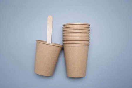 Wooden and cardboard disposable tableware on a gray background. Environmentally friendly products. Фото со стока