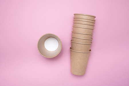A stack of paper cups for hot drinks on a pink isolated background.