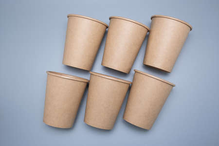 Disposable paper cups on a gray background. Environmentally friendly product.