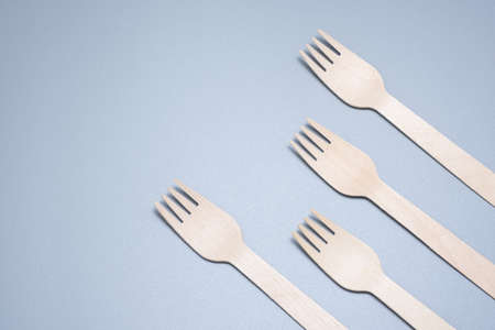 Wooden disposable fork on a gray background close-up. Environmentally friendly product. Фото со стока