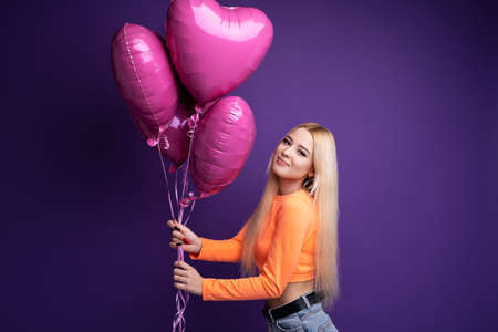 Happy blonde with heart-shaped balloons on a purple background in the studio. Valentines Day.