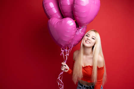 Beautiful smiling girl with balloons on a red background. Valentines day for all lovers. Фото со стока
