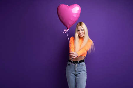 Happy blonde with heart-shaped balloons on a purple background in the studio. Valentines Day February 14. Фото со стока