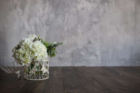 White flowers in a white cage stand on a wooden floor on a gray background. Bridal bouquet