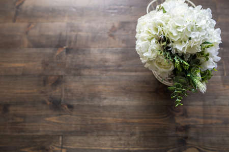 White flowers on a brown wooden floor. View from above