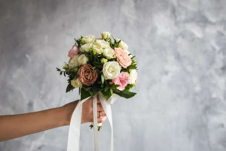 The bride is holding a wedding bouquet on a gray background Фото со стока