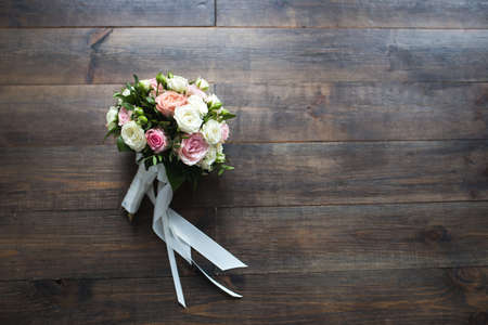 Female hand holding a wedding bouquet on a dark background