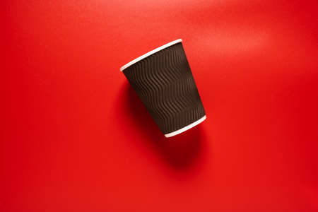 Brown paper cup for coffee or tea on a red background.
