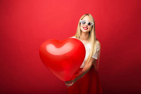 Beautiful and positive blonde with a balloon in the form of a heart on a red isolated background.