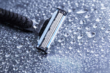 Razor close-up with water drops on a gray background.