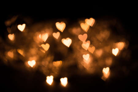 Blurred background, bokeh in the form of a heart of yellow warm color.