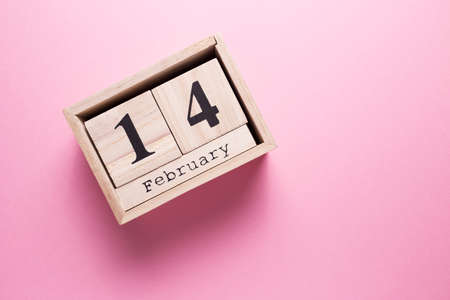 Wooden calendar with the inscription February 14 on a pink isolated background.