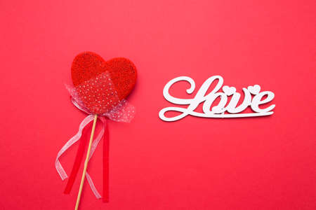 Lettering from wooden letters love on a red isolated background. Heart in the form of candy on a stick.