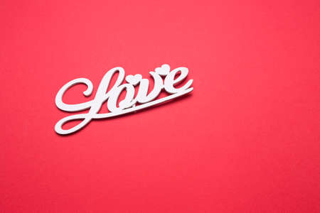 Lettering from wooden letters love on a red isolated background. Romantic postcard. Stock fotó