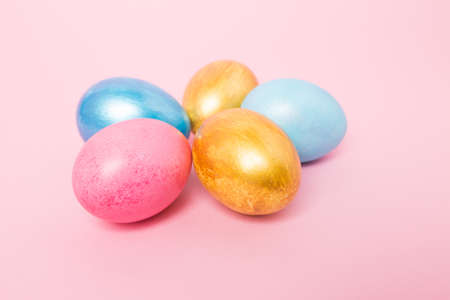 Multi-colored Easter eggs on a pink isolated background. Easter is a bright holiday.