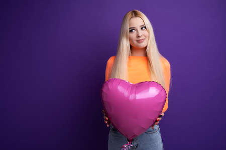 Happy blonde with heart-shaped balloons on a purple background in the studio. Valentines Day February 14. Stock fotó