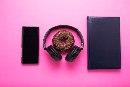 A pink background on which lies a laptop phone donut and wireless headphones. Office lunch concept.