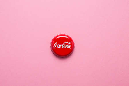 Kiev, Ukraine - June 12, 2020: classic cap close-up of Coca-cola. Cap of cola on a pink background. Sajtókép