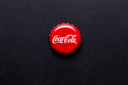 Kiev, UKRAINE - January 28, 2019: classic cap close-up of Coca-cola. Coca cola cap on a black background.
