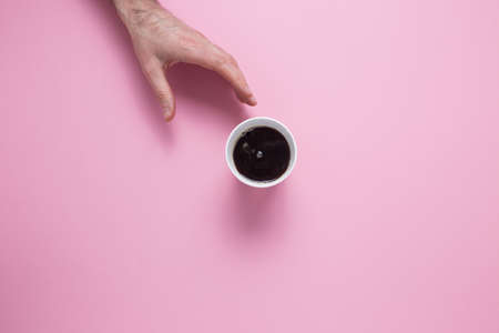 A male hand reaches for a glass with a coffee on a pink background. View from above. Stock fotó