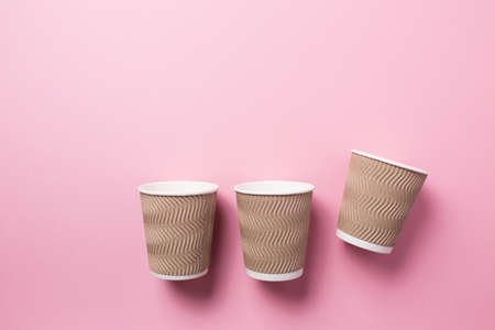 Paper cup for hot coffee or tea on a pink isolated background.
