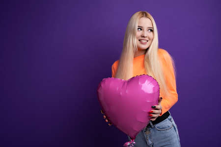 Beautiful blonde with a heart-shaped balloon on a purple background in the studio. Valentines Day February 14. Stock fotó