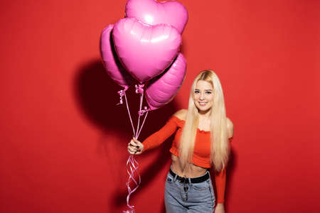 Beautiful smiling girl with balloons on a red background. Valentines day for all lovers. Stock fotó