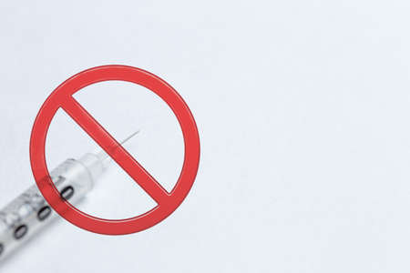 No vaccination. Syringe on a white background with a red sign prohibited.