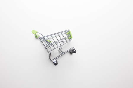 Grocery cart with light green handles on a white isolated background close-up.
