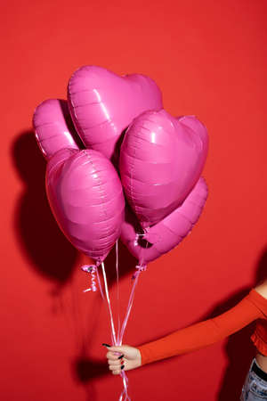 A female hand holds an inflatable purple heart-shaped balloons. Picture taken in the studio on a red background.