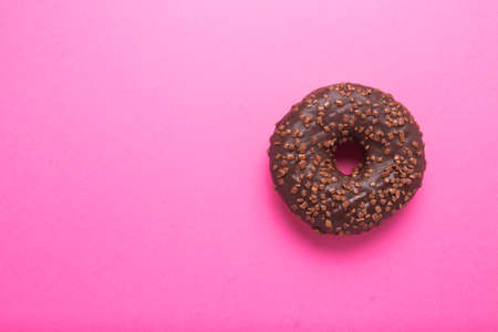 Chocolate donut on a pink background close-up.