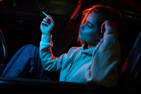 Sad girl in neon light in a car with a cigarette.