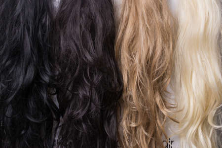 Womens wigs of different shades. Blonde brunette brown-haired woman.