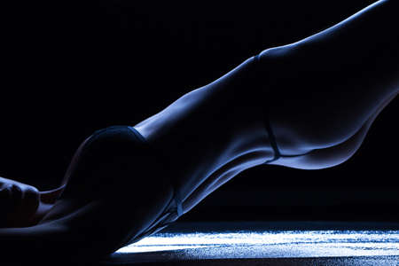 Luxurious female body in blue light in studio on a black background
