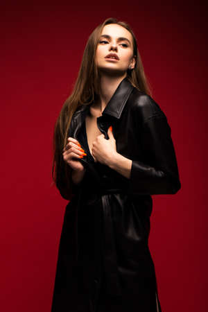 Portrait of a young beautiful girl in a black leather coat over a red background.