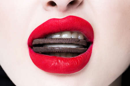 Red lips with biscuits in the mouth closeup