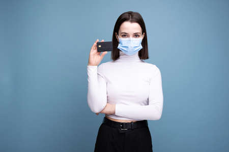 Girl in a medical mask with a bank card on a blue background. Online shopping due to the pandemic.