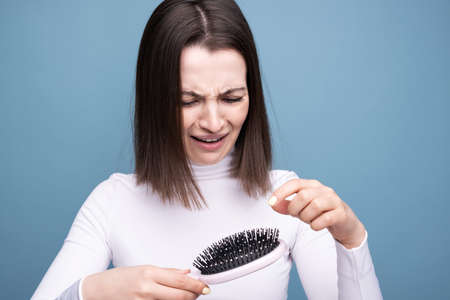 Brunette with a comb in her hands in shock from hair loss. Studio portrait blue background. Stockfoto