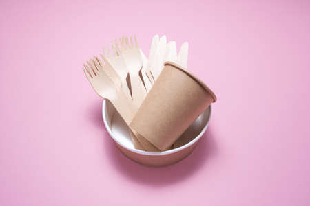 Wooden and cardboard disposable tableware on a pink background. Environmentally friendly products.