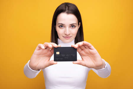 Close up portrait of young smiling business woman holding credit card, isolated on yellow background.
