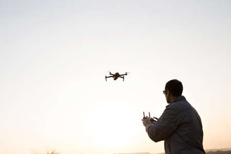 A man launches a drone into the sky. Stockfoto