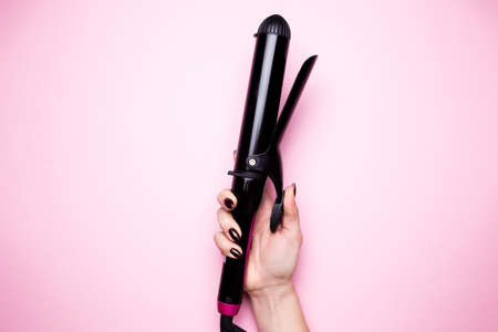 Female hand holds a hair curler in black on a pink isolated background close-up. Stockfoto