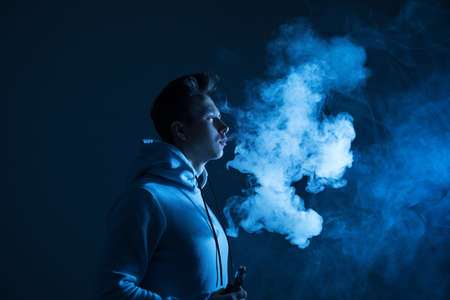 A young guy smokes a vape in the studio in neon light.