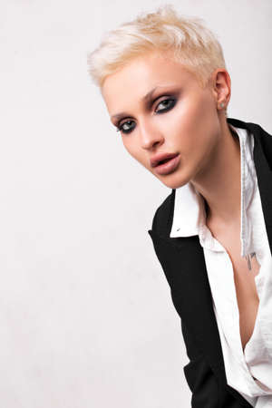 Blonde with short hair and smoky ice on a white background in the studio.