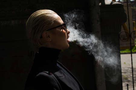A beautiful girl smokes a vape and lets out smoke Stock fotó