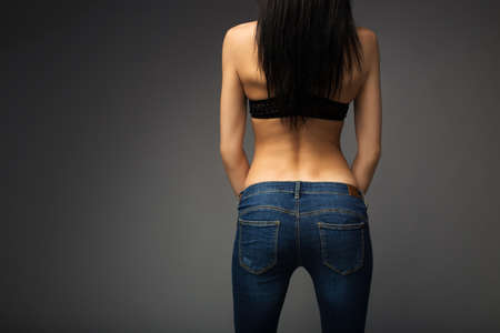 Lovely young beautiful brunette stands with her back to the camera. In blue jeans. Stock fotó