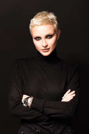 Portrait of a short-haired blonde on a black background.