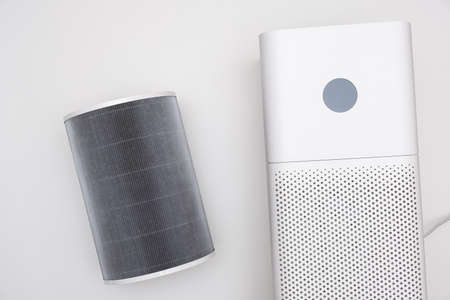 Indoor air purifier of white color close-up on a white background. Dust and allergy cleaner in the house.