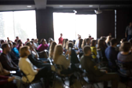 Blurred photo of people at the training. Workshop with lots of people.