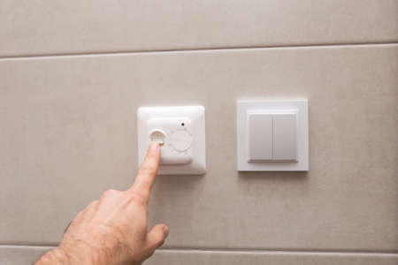 The male hand adjusts the temperature. The regulator of heating of a heat-insulated floor in a bathroom.